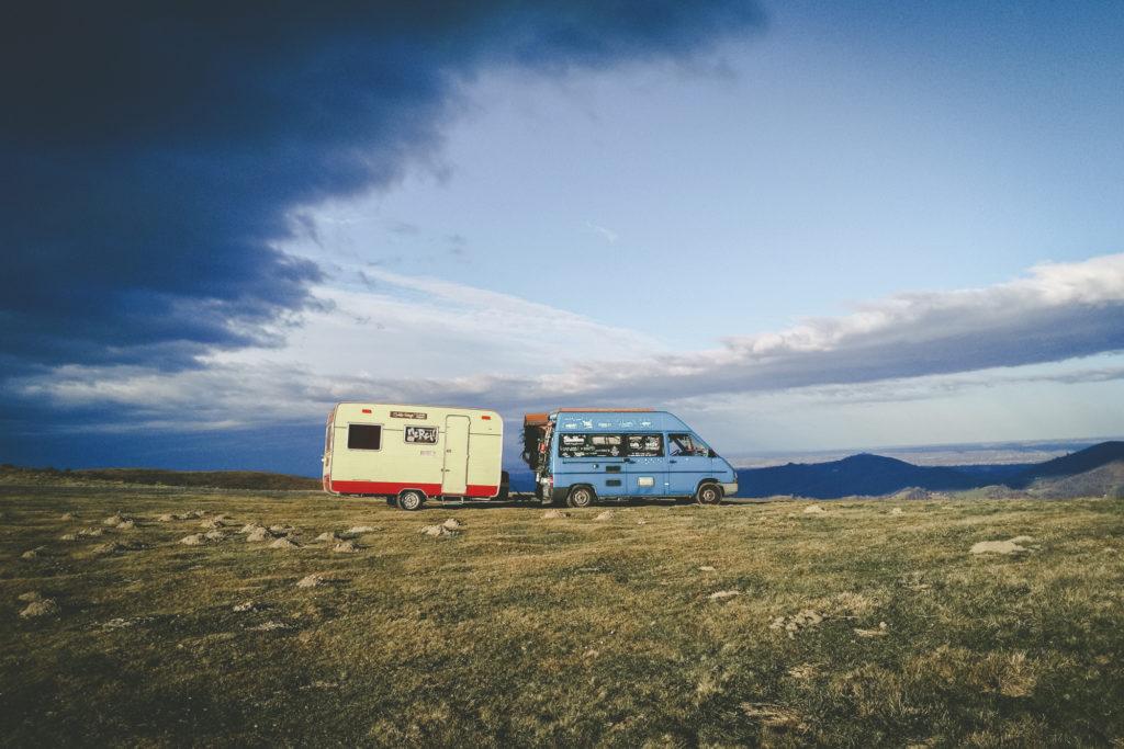 Le fourgon bleu aménagé, avec la caravane jaune mini-cinéma nomade.