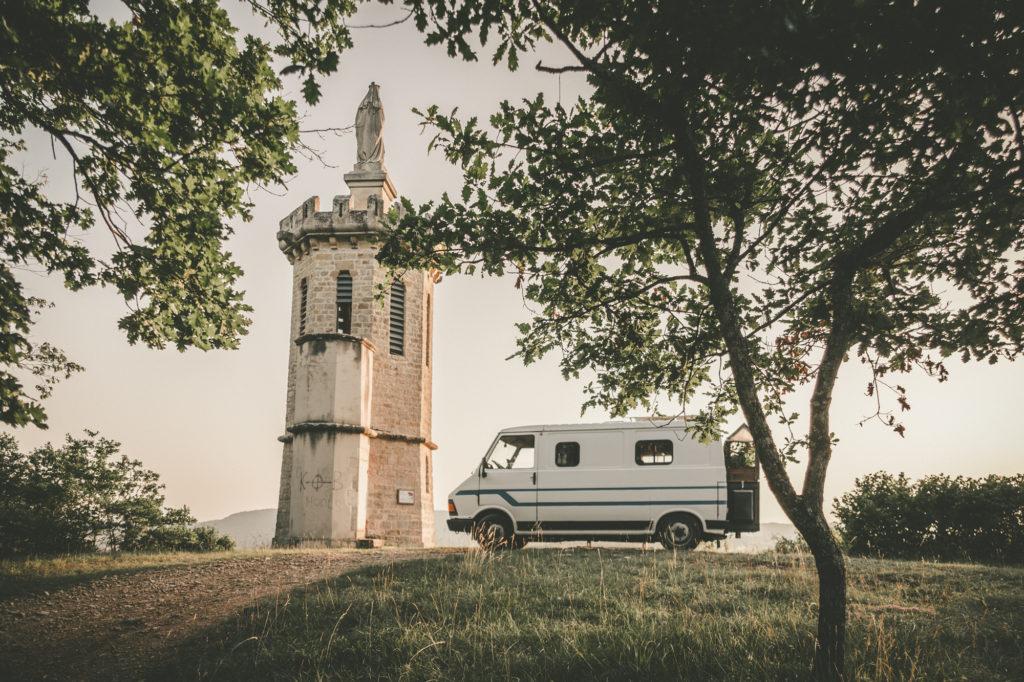 Popeye, le fourgon aménagé, près d'une tour dans la campagne