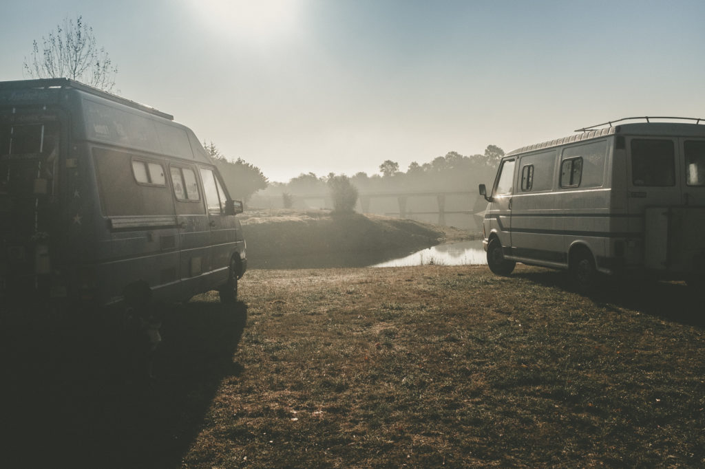 Le camion bleu et Popeye, l'autre fourgon aménagé, près d'un lac dans la nature.